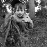 Kind kauernd im Wald